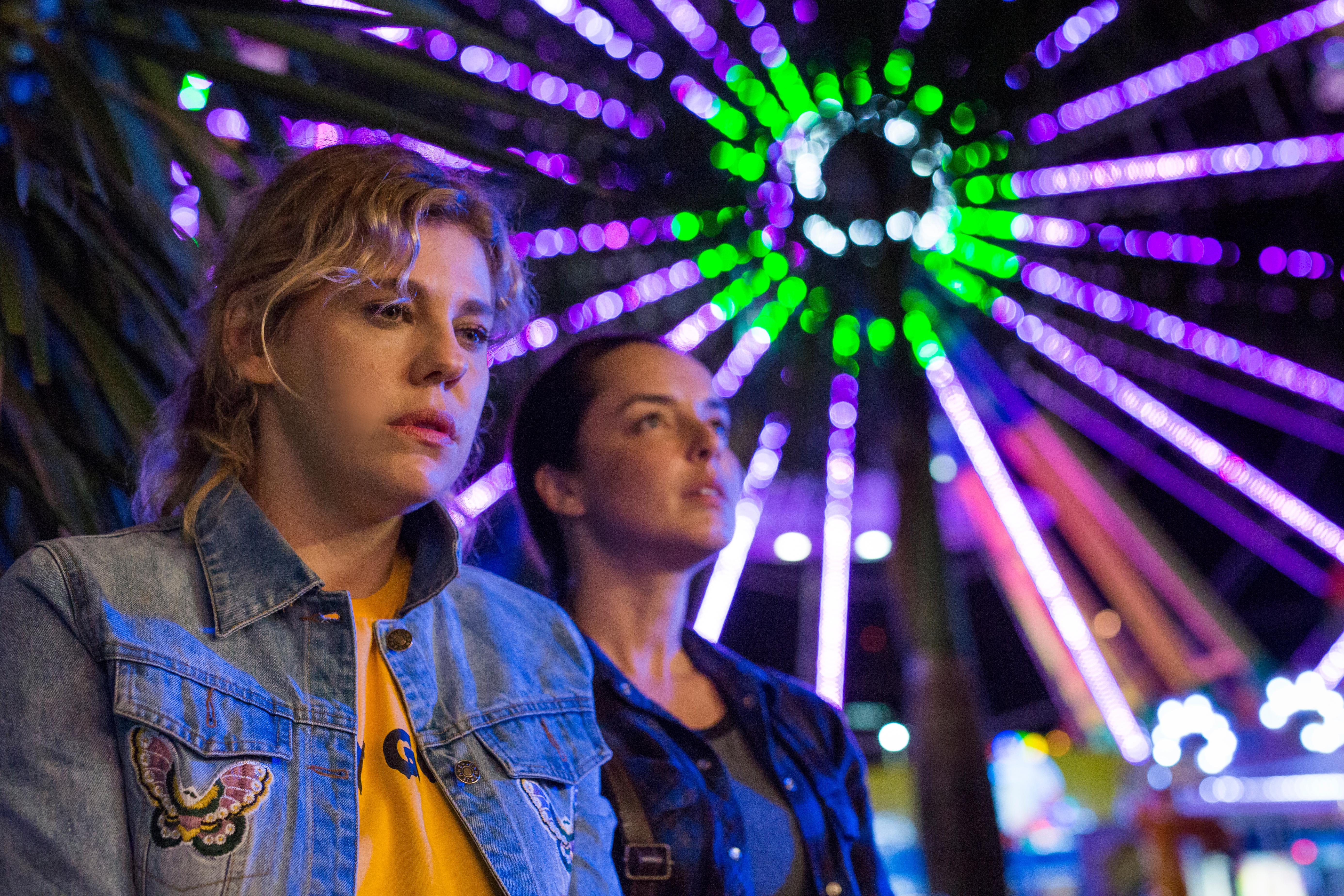 Cena de Por que Você não Chora? Bárbara Paz a frente e Carolina Monte Rosa logo atrás com uma roda gigante iluminada ao fundo.
