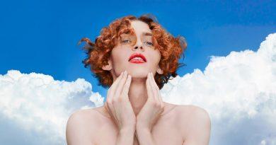 Imagem de Sophie em um cenário azul com nuvens ao fundo.