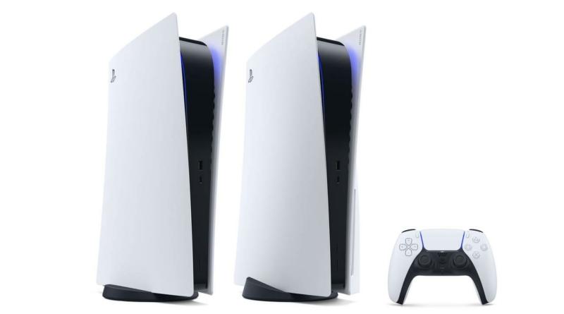 Imagem com fundo branco mostrando dois playstation 5 brancos de pé e um controle no canto inferior direito